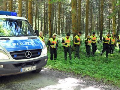 Polizisten durchsuchen bei Heidenheim-Nietheim ein Waldstück, an dessen Rand die Leiche der entführten Bankiersfrau gefunden worden war.