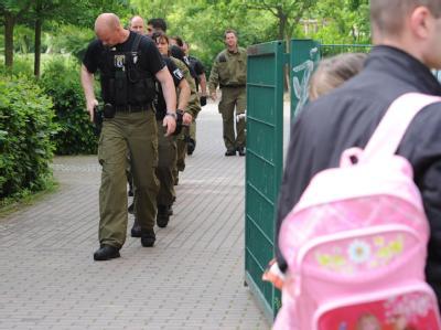 Polizeibeamte gehen über den Hof der Berliner Schule, an der Amok-Alarm ausgelöst worden war.