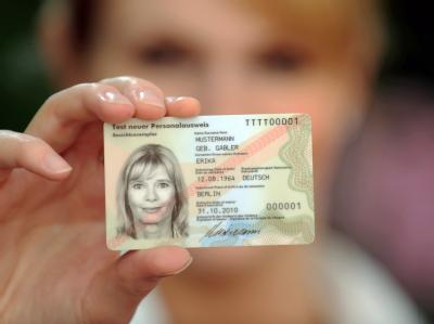 Eine Frau zeigt in der Bundesdruckerei ein Muster des neuen Personalausweises.
