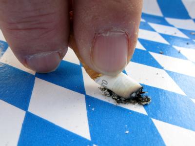 ILLUSTRATION - Eine Zigarette wird am 03.12.2009 in München (Oberbayern) auf einem Rautenmuster ausgedrückt. Nach dem positiven Volksentscheid über ein totales Rauchverbot in bayerischen Gaststätten wollen die Initiatoren bundesweit aktiv werden. Das künd