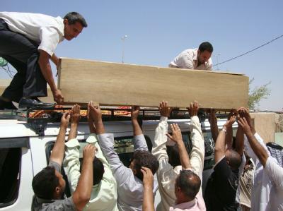 Helfer heben einen Holzsarg auf einen Minibus. Bei Bombenanschlägen in mehreren Stadtvierteln Bagdads sind mehr als 60 Pilger zu Tode gekommen.