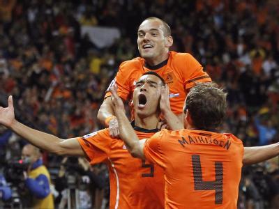 Giovanni van Bronckhorst (M.) feiert mit seinen Mannschaftskameraden Wesley Sneijder (oben) und Joris Mathijsen (r.) den Führungstreffer im Halbfinale gegen Uruguay.