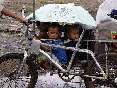 Eine Frau bringt ihre Kinder und ein paar Habseligkeiten in Sicherheit. nachdem ein Taifun ihr Haus zerstört hat.