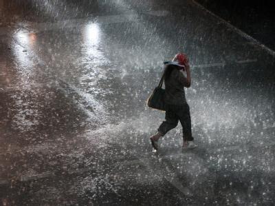 Eine Frau läuft während eines Gewitters mit einer Plastiktüte über dem Kopf über eine Kreuzung in Köln.