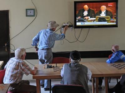 Kosovaren schauen sich die Urteilsverkündung durch den IGH in Pristina im Fernsehen an.