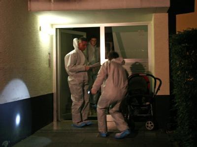 Polizisten untersuchen Spuren an einem Hauseingang.