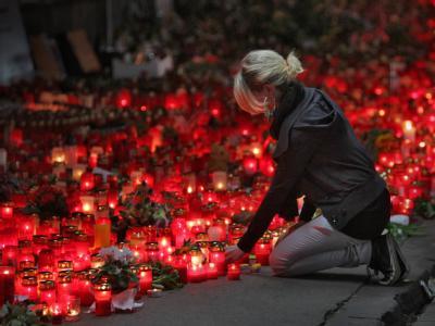 Nach der Loveparade-Katastrophe: Eine Frau stellt in Duisburg an der Unglücksstelle der Loveparade eine brennende Kerze ab.