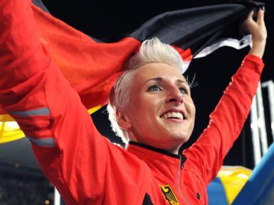 Die deutsche Hochspringerin Ariane Friedrich reisst die Arme hoch und jubelt mit der Flagge.