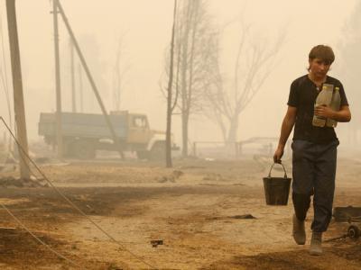 Ein Junge mit Wasserflaschen in einem von den Flammen zerstörten Dorf in Russland.
