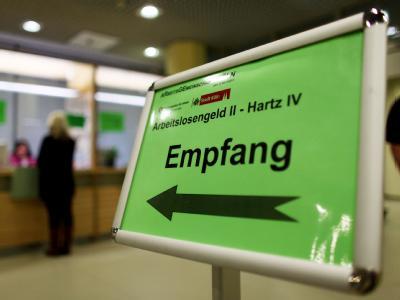 Eine Frau informiert sich am Empfangsschalter einer Arbeitsagentur über die Beantragung von Hartz IV.