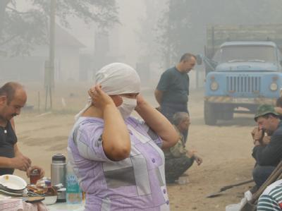Mit einer Maske versucht diese Frau, sich vor dem stark gesundheitsgefährdenden Rauch zu schützen.