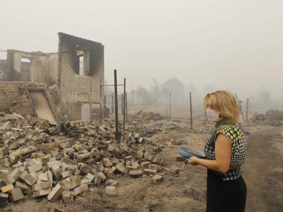 Eine Bewohnerin der Region Nischni Nowgorod steht fassungslos vor ihrem niedergebrannten Haus.