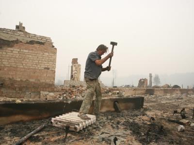 Ein Bewohner sucht in den Trümmern, die das Feuer hinterlassen hat, nach seinem Hab und Gut.