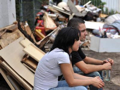 Helfer pausieren während der Aufräumarbeiten nach der Überflutung des Chemnitzer Ortsteils Harthau. Für viele Betroffene wird das Ausmaß der Schäden jetzt erst richtig deutlich.