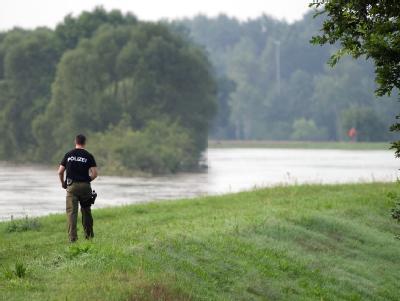 Ein Polizeibeamter geht über den Deich unweit von Klein Bademeusel,.