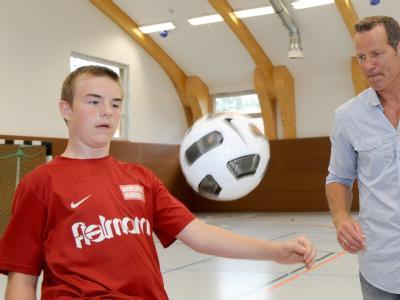 Der Ex-Boxweltmeister Henry Maske spielt mit dem 14-jährigen Dennis Fußball.(Archivbild vom 12.08.2010). Er lädt Jugendliche mit Hilfe seiner Stiftung für eine Woche zum Feriencamp nach Brandenburg ein.