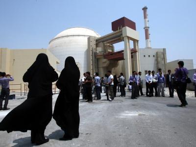 Iranische Frauen und Sicherheitspersonal vor dem neuen Atomkraftwerk in Buschehr.