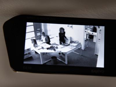 Eine Videokamera zeichnet in einer gestellten Szene die Arbeit in einem Büro auf.