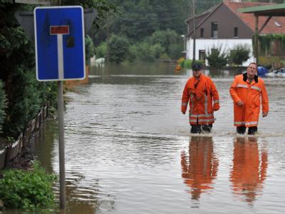 Zwei Feuerwehrleute waten im Landkreis Osnabrück durch eine überschwemmte Straße.