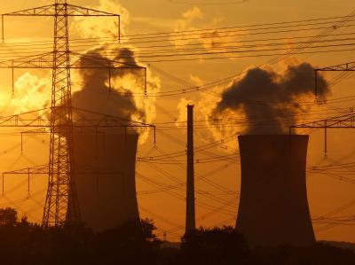 Die untergehende Sonne hinter den Kühltürmen eines Atomkraftwerks.