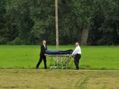 Nach dem Familiendrama  transportieren Bestatter im nordhessischen Trendburg-Eberschütz eine Leiche ab.