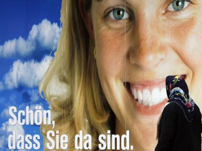 Eine Frau mit Kopftuch vor einem Werbeplakat in Berlin.