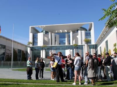 Touristen stehen vor dem Bundeskanzleramt in Berlin, während im Gebäude Spitzen der Koalition über die Zukunft der Atomkraft diskutieren.