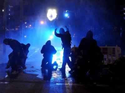 Randalierer stehen nach dem Schanzenfest im Schanzenviertel in Hamburg vor einen Wasserwerfer der Polizei.