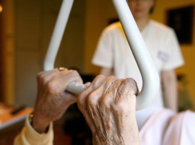 Eine Bewohnerin in einem Seniorenzentrum hält sich in ihrem Bett an einem Haltegriff fest (Foto vom 24.09.2009): Minister Rösler plant umfassende Reformen in der Pflege.