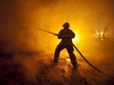 Ein Feuerwehrmann kämpft mit Löschwasser gegen die Flammen an.