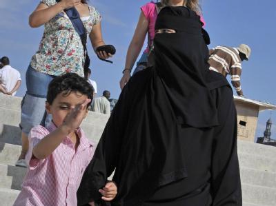 Eine Frau mit Burka in Paris: Künftig ist das Tragen von Vollschleiern wie Burka und Nikab in Frankreich gesetzlich verboten (Archivbild).