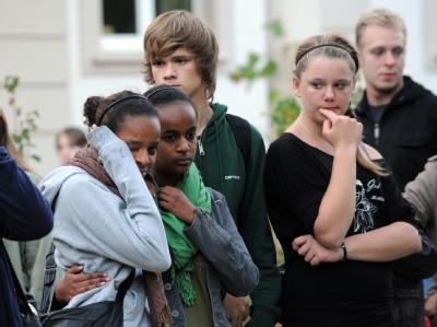 Jugendliche stehen am Montag in Lörrach vor dem Elisabethen-Krankenhaus und gedenken der Opfer des Amoklaufs.