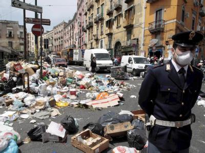 Hier hilft nur noch ein Mundschutz: Ein Polizist vor Müllbergen in einer Straße in Neapel (Archivfoto vom 16.05.2008).