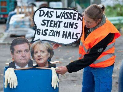 Eine Aktivistin der Protestbewegung Parkschützer befestigt in Stuttgart ein Bild von Bundeskanzlerin Angela Merkel und Baden-Württembergs Ministerpräsident Stefan Mappus (beide CDU). Mappus und Merkel zeigen bei den Protesten um das umstrittene Bahnprojek
