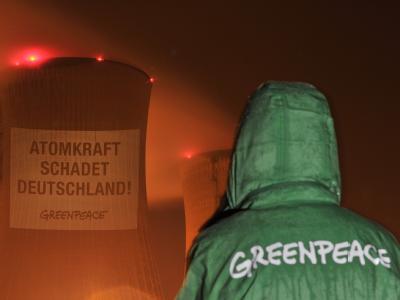 Eine Greenpeace-Aktivistin vor dem Kühlturm eines Atomkraftwerks. (Archivbild)