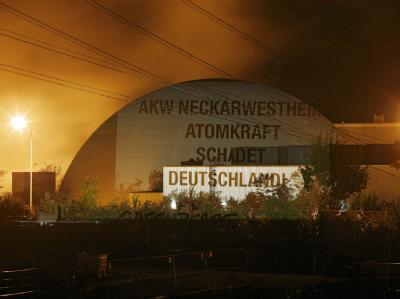 Der Spruch «AKW Neckarwestheim: Atomkraft schadet Deutschland» ist in Neckarwestheim auf das Reaktorgebäude des AKW Neckarwestheim projiziert.