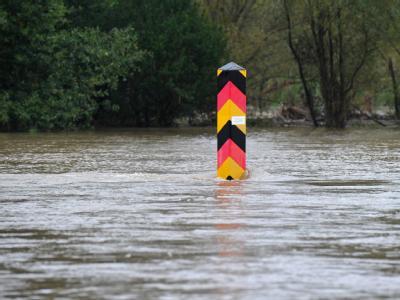 Ein Grenzpfeiler am Ufer der Neiße im südostbrandenburgischen Klein Bademeusel steht im Hochwasser des deutsch-polnischen Grenzflusses. Die Hochwasserlage im Süden Brandenburgs spitzt sich weiter zu.