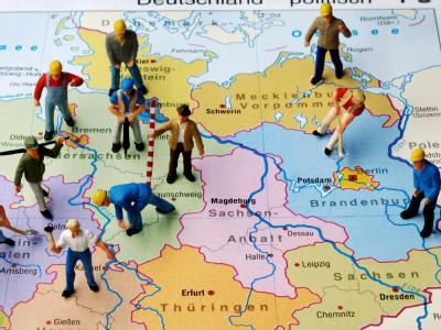 Kleine Plastikfiguren stehen auf einer Landkarte von Deutschland verteilt auf die Bundesländer - gerade ein Drittel der Figuren stehen auf der ostdeutschen Kartenseite. Insgesamt schrumpfte die Bevölkerung in den neuen Bundesländern um ganze 1,7 Millionen