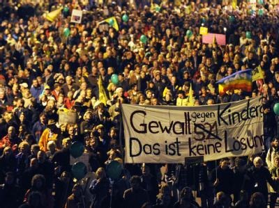 Demonstranten tragen am Freitag während einer Großdemonstration in Stuttgart ein Transparent mit der Aufschrift «Gewalt gegen Kinder. Das ist keine Lösung».