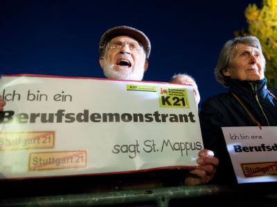 Gegner des Bahnprojekts Stuttgart 21 halten am Freitagabend im Stuttgarter Schlossgarten ein Plakat mit der Aufschrift «Ich bin ein Berufsdemonstrant» in den Händen.