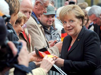 Bundeskanzlerin Merkel gibt im Rahmen der zentralen Feierlichkeiten zum Tag der deutschen Einheit in Bremen Zuschauern am Absperrgitter Autogramme.