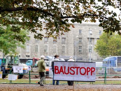 Auf einem Protestplakat im Schlossgarten in Stuttgart fordern Gegner des milliardenschweren Bahnprojekts Stuttgart 21 einen Baustopp.