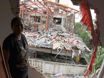 Eine thailändische Frau schaut geschockt aus ihrem beschädigten Haus: Bei der Explosion in Bang Bua Thong 40 Kilometer nördlich von Bangkok sind drei Menschen ums Leben gekommen.