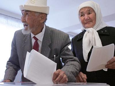 Ein älterer kirgisischer Mann wirft seinen Stimmzettel bei den Parlamentswahlen in Bischkek in die Wahlurne.