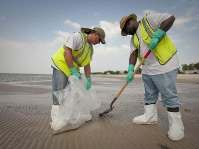 Frank McNell (l-r) und Darelle McKinnon reinigen den Strand in Longbeach, Mississippi. Noch immer sind weite Teile der US-Küste am Golf von Mexiko vom Öl verseucht. (Archivbild)