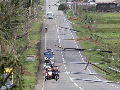 Auf einer Straße im philippinischen Tumauini liegen umgeknickte Strommasten.