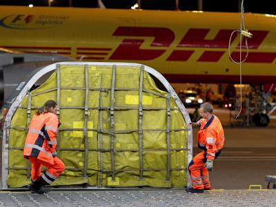 Ein DHL-Mitarbeiter zieht in den Nachtstunden einen Luftfrachtcontainer zum Entladen ins DHL Hub auf dem Flughafen Leipzig/Halle. (Archivfoto)