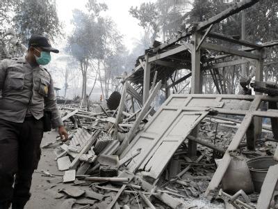 Ein Polizist sucht in den Trümmern eines Hauses nach Opfern.