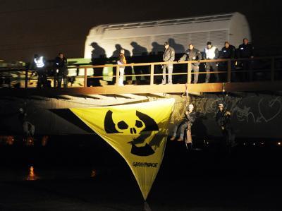 Ein Zug mit 11 Castor-Behältern verlässt den Bahnhof im badischen Kehl. Unter der Brücke haben sich Greenpeace-Aktivisten angeseilt.