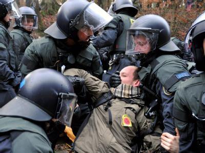 Polizeikräfte schleppen einen Demonstranten weg.